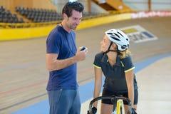 Cycliste féminin parlant à l'entraîneur photographie stock libre de droits