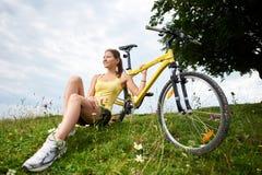 Cycliste f?minin attirant avec la bicyclette jaune de montagne, appr?ciant le jour ensoleill? dans les montagnes photo stock