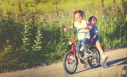 Cycliste heureux de fille de soeur d'enfants montant un vélo Photos libres de droits