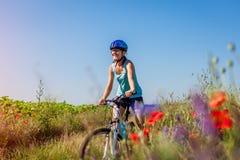 Cycliste heureux de jeune femme montant une bicyclette de montagne dans le domaine d'été Fille ayant les jambes de levage d'amuse images stock