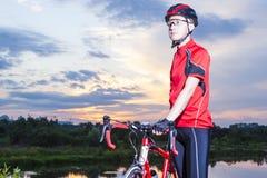 Cycliste masculin avec son vélo de route posant dehors à l'heure d'or Image stock