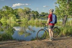 Cycliste masculin avec un vélo de montagne sur un rivage de lac Image stock