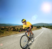 Cycliste masculin montant un vélo sur une route ouverte un jour ensoleillé Photos stock