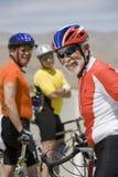 Cycliste masculin supérieur avec des amis se tenant à l'arrière-plan Photographie stock