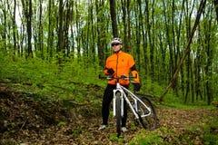 Cycliste montant le vélo dans la belle forêt de ressort Photographie stock