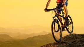 Cycliste montant le vélo en bas de la roche au coucher du soleil Sport extrême et concept faisant du vélo d'Enduro Images libres de droits