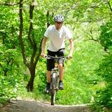 Cycliste montant le vélo sur la traînée dans la forêt Photo libre de droits