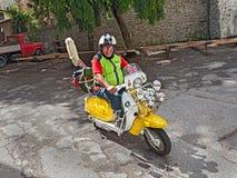 Cycliste montant un scooter Lambretta de vintage Photos libres de droits