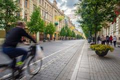Cycliste passant vite par sur la rue commerciale principale de Vilnius photographie stock
