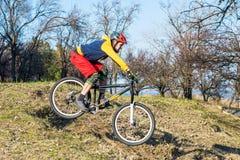 Cycliste professionnel dans un chandail jaune et un shertakh rouge entraînant une réduction une colline, l'espace libre Style de  photos stock