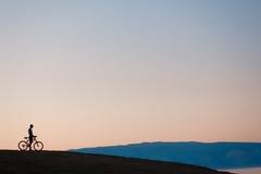Cycliste regardant le coucher du soleil Photos libres de droits