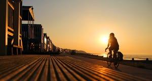 Cycliste silhouetté à la plage Photos stock