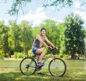 Cycliste supérieur montant un vélo en parc Photographie stock libre de droits