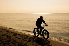 Cycliste sur le bord de la mer dedans Image stock