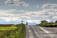 Cycliste sur une route à distance Photo stock