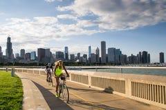 Cyclistes Chicago pendant le coucher du soleil Images stock