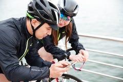 Cyclistes de femme et d'homme à l'aide du smartphone ensemble Photos libres de droits