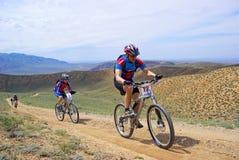 Cyclistes de montagne emballant sur la route rurale dans le désert photographie stock