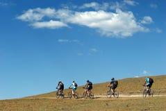 Cyclistes de montagne sur la route rurale Photos libres de droits