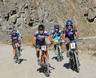 Cyclistes de montagne vers le haut sur la route rurale dans les roches image libre de droits