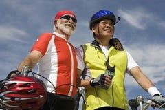 Cyclistes masculins supérieurs se tenant contre le ciel Images libres de droits