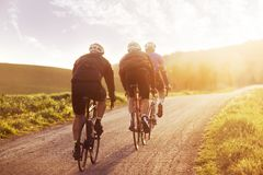 Cyclistes montant dans le coucher du soleil en Toscane images libres de droits