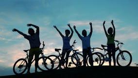 Cyclistes ondulant avec des mains au ciel de coucher du soleil clips vidéos