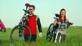 Cyclistes portant des vélos par la haute herbe banque de vidéos