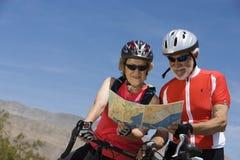 Cyclistes supérieurs lisant la carte ensemble Photo stock