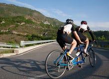 Cyclistes sur une bicyclette tandem montant vers le haut sur une chaussée de montagne Image libre de droits