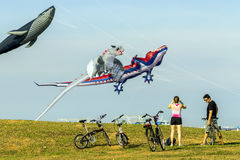 Cyclists admire large flying multi colored kites at East Coast Park Stock Photos