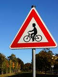 Cyclists ahead sign. Trees and blue sky background Stock Photography