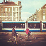 Cyclists in Amsterdam. Young male and female cyclists on bicycles on a street in Amsterdam with a tram in background royalty free stock photos