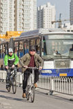Cyclists in Beijing downtown with a bus on the background, China Royalty Free Stock Photo