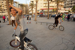Cyclists, Beirut. Cyclists, waterfront, Beirut. A Macdonalds can be seen in the background and palm trees are planted in designated spaces in the paving Stock Image