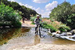 Cyclists on the bicycle trail. Cyclist is crossing the river with a mountain bike Stock Photo