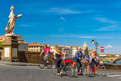 Cyclists on Bridge Santa Trinita, Florence, Italy Stock Photo
