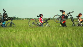Cyclists carrying bikes through high grass stock video