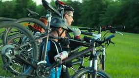 Cyclists carrying bikes through high grass stock video footage