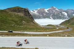 Cyclists climbing mountain pass against snowcapped mountains stock image