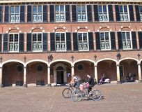 Cyclists in a cobbled piazza stock image