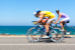 Cyclists competition along a coastal road royalty free stock photography