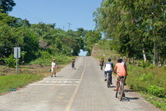 Cyclists on countryside road. Scenic view of cyclists and pedestrians on countryside road, Leon Viejo, Nicaragua royalty free stock image