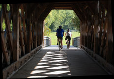 Cyclists crossing covered bridge, Guelph Royalty Free Stock Images