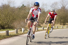 Cyclists in a curve. Two cyclists leaning inwards in the curve of a road during a training tour on a sunny spring day Royalty Free Stock Image