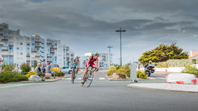 Cyclists in a curve during a road bike race. Saint Gilles Croix de Vie, France - September 10, 2016 : Final triathlon championship of France in the category D3 royalty free stock photo