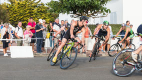 Cyclists in a curve during a road bike race. Saint Gilles Croix de Vie, France - September 10, 2016 : Final triathlon championship of France in the category D3 royalty free stock image