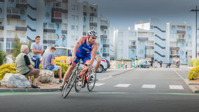 Cyclists in a curve during a road bike race. Saint Gilles Croix de Vie, France - September 10, 2016 : Final triathlon championship of France in the category D3 stock image
