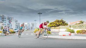 Cyclists in a curve during a road bike race. Saint Gilles Croix de Vie, France - September 10, 2016 : Final triathlon championship of France in the category D3 royalty free stock photography