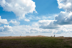 Cyclists in the distance against the sky. Mountain landscape. The shadow on the ground. Impressive skies. Royalty Free Stock Photography